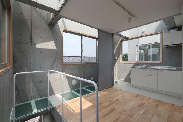 強化合わせガラスの床とキッチン部分が構造上の工夫により生まれた空間。天窓から陽光が注ぐ