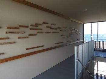 ルーバー端材に海や山のイラスト。窓からは海が望める