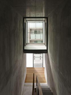 3階の共用廊下。ガラス張りの空間は、3階住戸の廊下部分。廊下をはさみ右側に居室、左側にバス・トイレがある