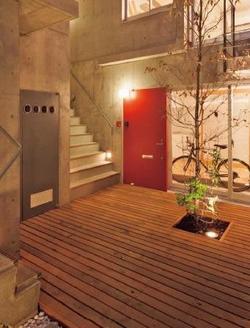 住民同士が必ず顔を合わせるコモンデッキ。直入りの赤い玄関の横に、他の部屋に通ずる階段が見える.jpg