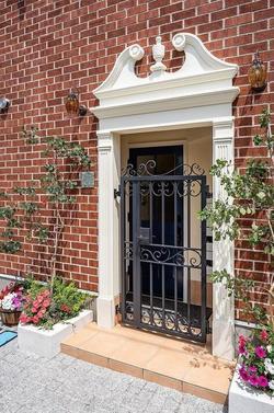 ロートアイアン(鍛鉄)の門扉。宅配ロッカーも完備。花の植栽はオーナーが用意した