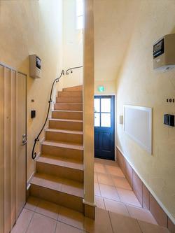 木目調の玄関ドア(手前)、共有部階段の手すりなど細部までこだわった
